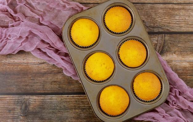 Six petits gâteaux à la vanille dans une plaque à pâtisserie sur table en bois.