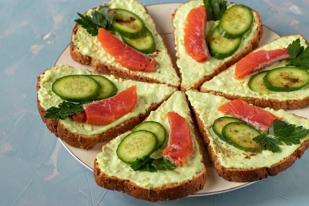 Six sandwichs avec de la pâte d'avocat, des concombres et du saumon salé sur une plaque sur fond bleu clair,