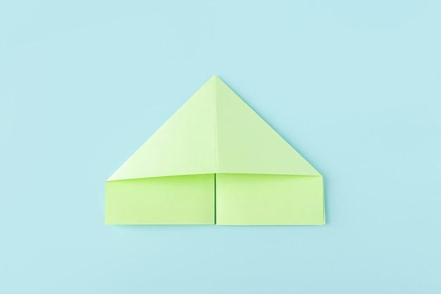 Sixième étape de la fabrication d'un papillon en papier origami avec du papier vert, des ciseaux sur fond bleu