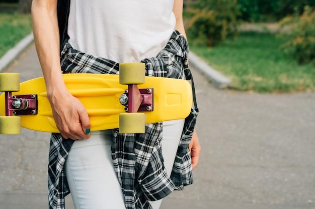 Skateboard en plastique jaune avec roues vertes dans les mains féminines à l'extérieur dans un parc