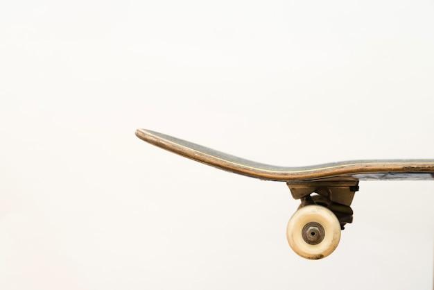 Skateboard professionnel sur la vue de côté de fond blanc.