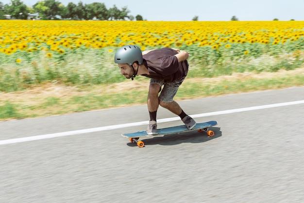 Skateur faisant un tour dans la rue de la ville en journée ensoleillée. jeune homme en équipement d'équitation et de longboard en action. concept d'activité de loisirs, sport, extrême, passe-temps et mouvement. aussi rapide qu'une voiture.
