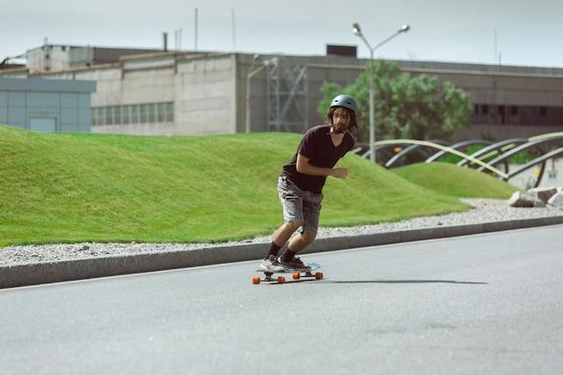 Skateur faisant un tour dans la rue de la ville en journée ensoleillée. jeune homme en équipement d'équitation et de longboard sur l'asphalte en action. concept d'activité de loisirs, sport, extrême, passe-temps et mouvement.