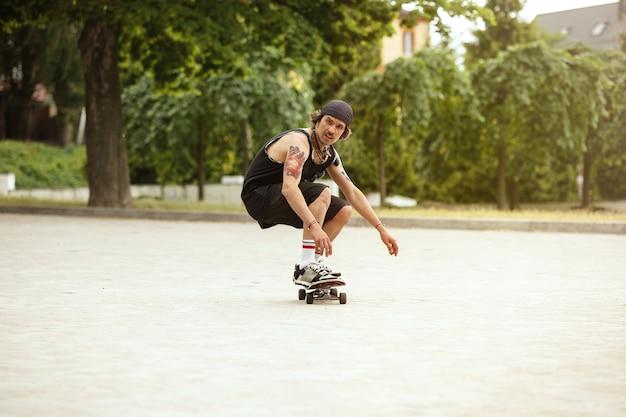 Skateur faisant un tour dans la rue de la ville en journée nuageuse. jeune homme en baskets et casquette équitation et longboard sur l'asphalte. concept d'activité de loisirs, sport, extrême, passe-temps et mouvement.