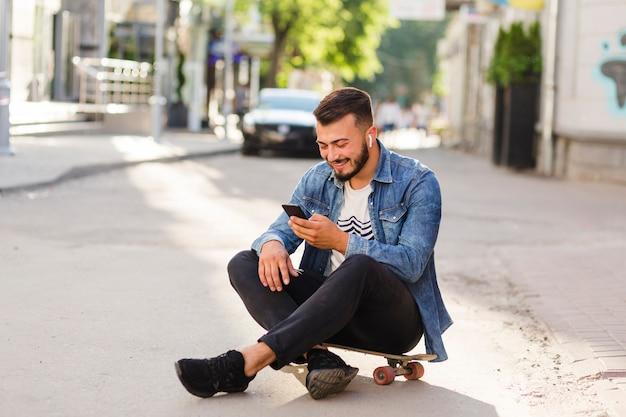 Skateur masculin assis sur une planche à roulettes en utilisant un téléphone mobile