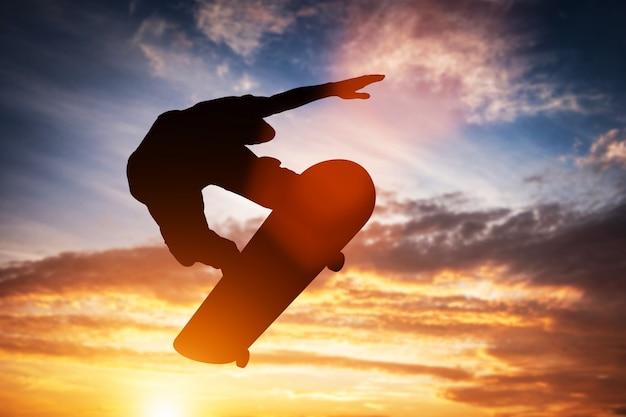 Skateur sautant au coucher du soleil.