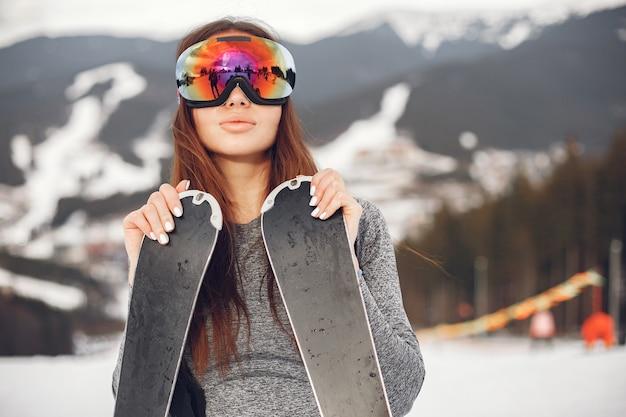 Ski brune jeune et active. femme dans les montagnes enneigées.