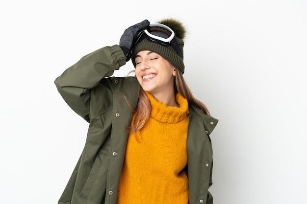 Skieur caucasien femme avec des lunettes de snowboard isolé sur fond blanc souriant beaucoup