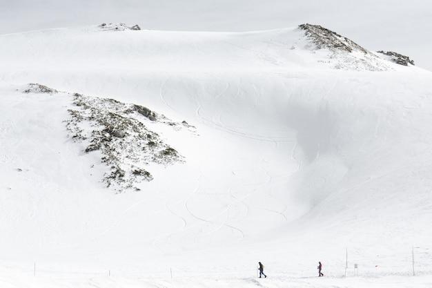 Skieurs marchant sur des chaînes de montagnes enneigées