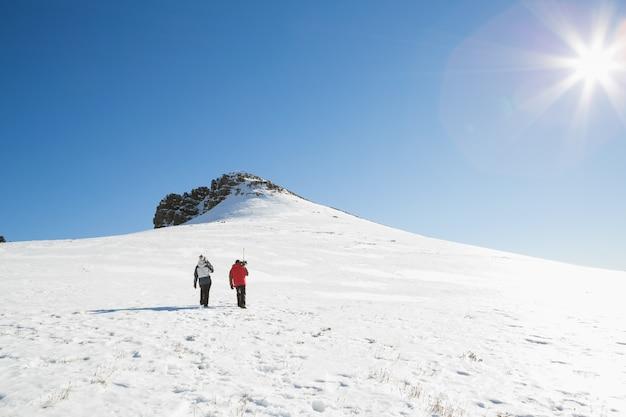 Skieurs marchant sur la neige par une journée ensoleillée