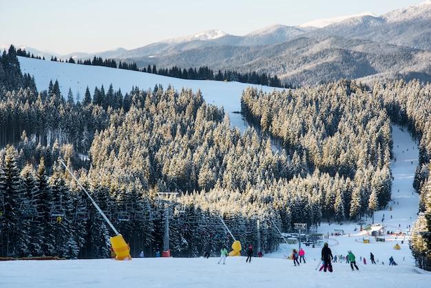 Skieurs et snowboarders descente en pente à la station de ski d'hiver sur fond de remontées mécaniques, forêts, collines au soir ensoleillé.