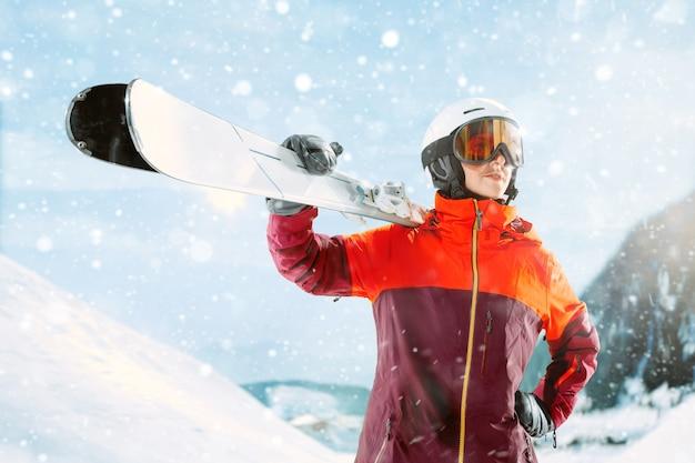 Skieuse debout avec un ciel dans une main sur fond de paysage de montagne magnifique. hiver, ski, neige, vacances, sport, loisirs, concept lifestyle