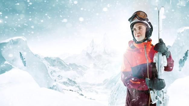 Skieuse debout avec un ciel dans une main sur fond de paysage de montagne magnifique