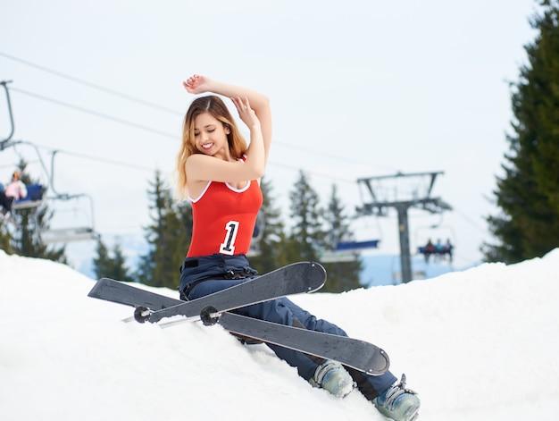 Skieuse mignonne femme assise au sommet de la colline enneigée avec équipement de ski à la station de ski. remontées mécaniques et forêt en arrière-plan. concept de saison de ski et de sports d'hiver