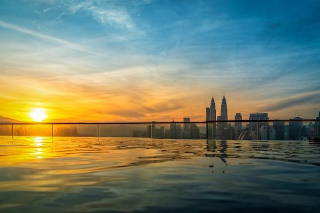 Skyline de la ville de kuala lumpur avec piscine sur le toit de l'hôtel au lever du soleil en malaisie.