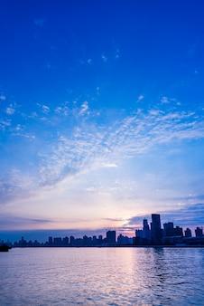 Skyline de la ville par la rivière contre le ciel nuageux