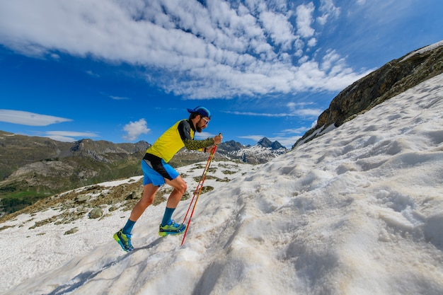 Skyrunner runner en montée dans un tronçon enneigé