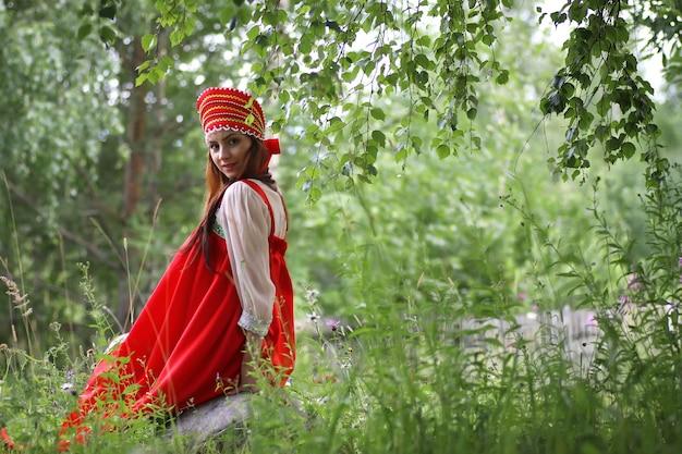 Slav en costume traditionnel est assis dans la nature