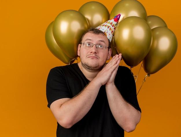 Un slave adulte anxieux dans des lunettes optiques portant une casquette d'anniversaire tient les mains ensemble et se tient devant des ballons à l'hélium
