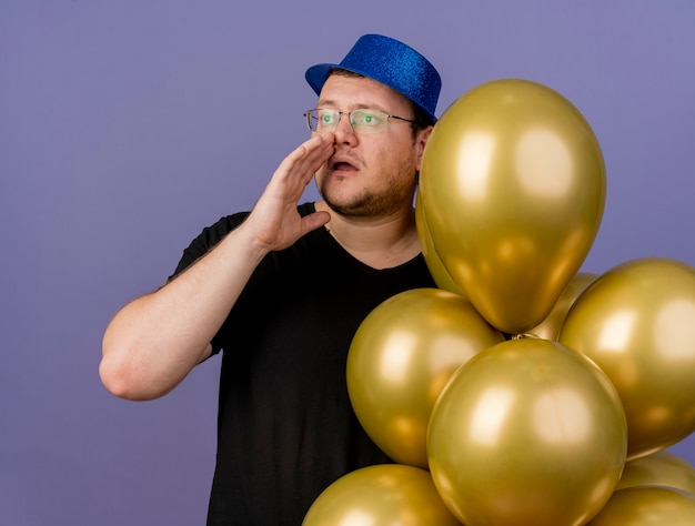 Un slave adulte anxieux dans des lunettes optiques portant un chapeau de fête bleu garde la main près de la bouche et tient des ballons à l'hélium