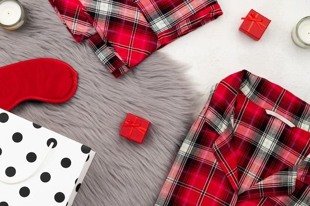 Sleapwear et accessoires pour femmes sur un couvre-lit moelleux gris. composition de mode maison vue de dessus plat laïque.