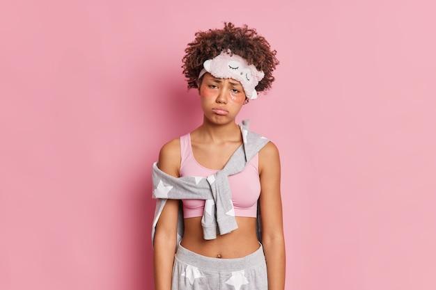 Sleepy fatigué frustré jeune femme afro-américaine applique des patchs de collagène sous les yeux pour le rajeunissement de la peau
