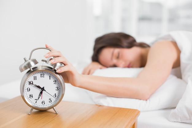 Sleepy floue femme dans son lit, étendant la main au réveil