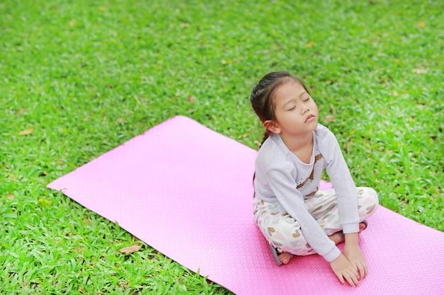 Sleepy petite fille assise sur un matelas rose dans la pelouse d'herbe verte.