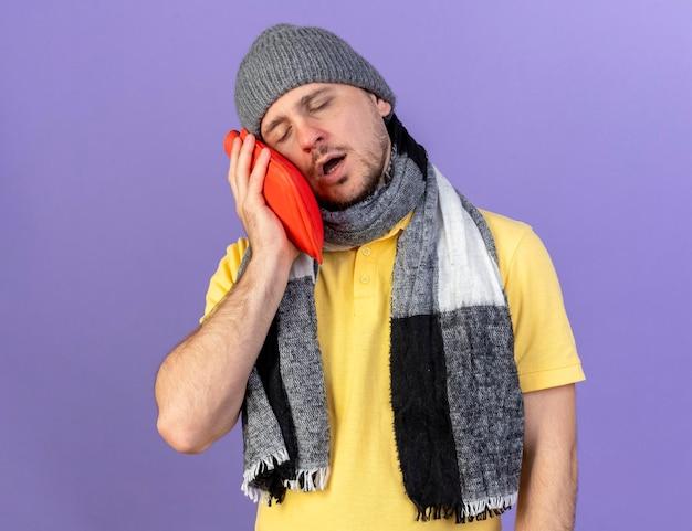 Sleepy young blonde homme slave malade portant un chapeau d'hiver et une écharpe