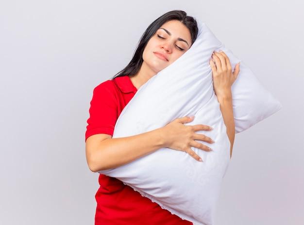 Sleepy young caucasian fille malade hugging oreiller mettant la tête dessus avec les yeux fermés isolé sur fond blanc avec copie espace