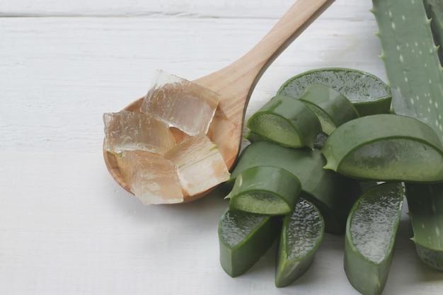 Slice aloe vera est dans une cuillère en bois posée sur un bois blanc.