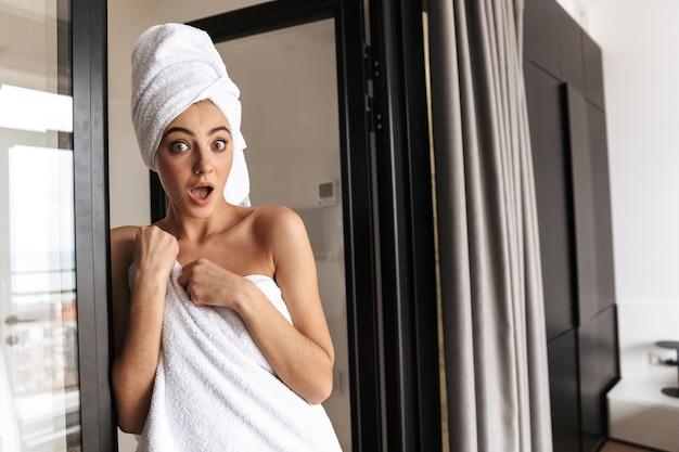 Slim belle femme portant une serviette blanche, debout dans la salle de bain après la douche dans la chambre d'hôtel