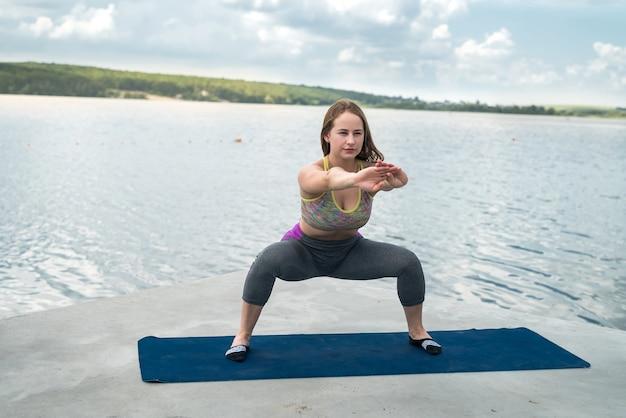 Slim belle femme en vêtements de sport pratique des poses de yoga sur un tapis au bord d'un lac par une journée d'été ensoleillée, fitness en plein air. concept de mode de vie sain