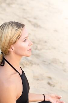 Slim femme d'âge mûr en noir pratiquant le yoga