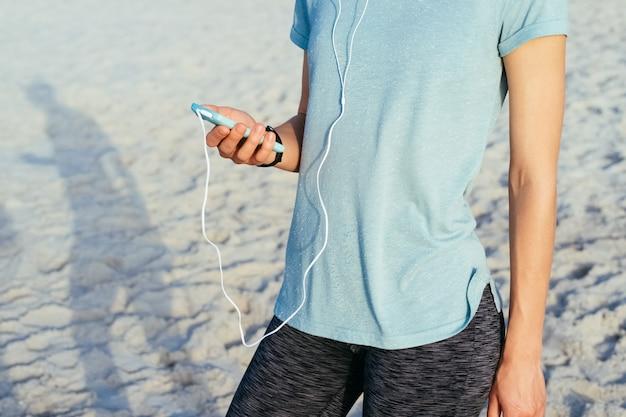 Slim femme dans une chemise bleue sur la plage, tenant un téléphone portable avec un casque