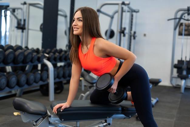 Slim femme exerce avec des haltères sur un banc au gymnase