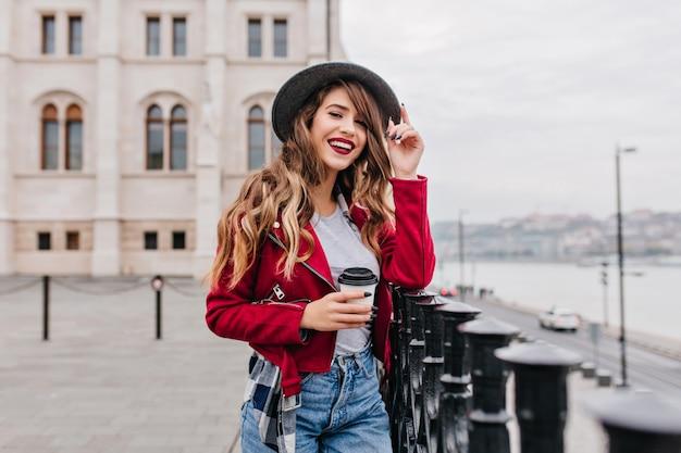 Slim femme avec grand sourire touchant son chapeau et tenant une tasse de latte sur la rue