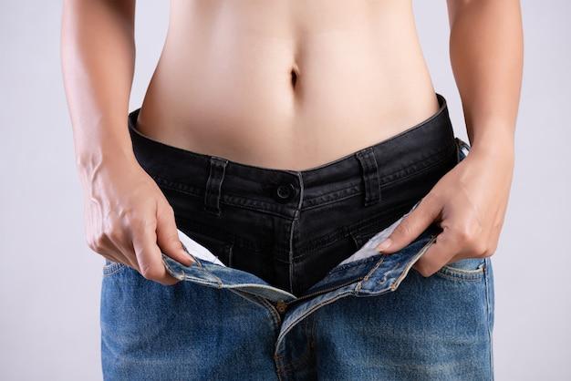 Slim femme en jeans bleu surdimensionné. concept de mode de vie santé et femme régime alimentaire