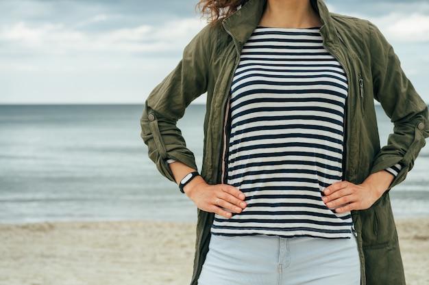 Slim femme en manteau vert et t-shirt rayé se dresse sur la plage contre la mer
