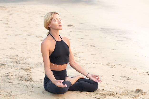 Slim femme mûre forte en noir pratiquant le yoga sur la plage de sable