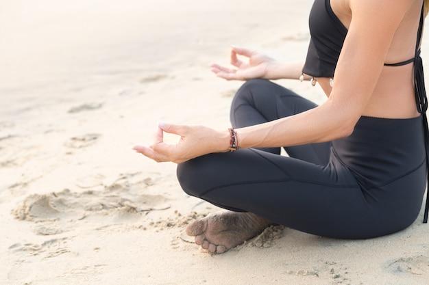 Slim femme mûre en noir pratiquant le yoga sur la plage de sable