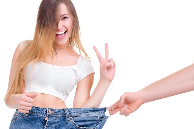 Slim femme revient avec un pantalon énorme et du ruban adhésif isolé sur blanc.