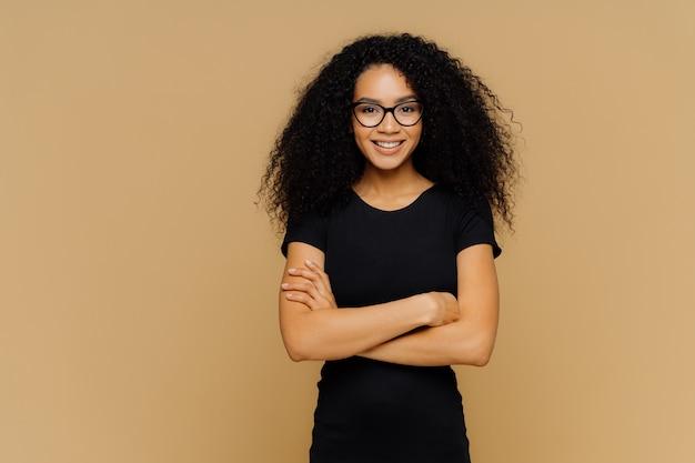 Slim femme satisfaite avec coupe de cheveux afro, porte des vêtements décontractés noirs, lunettes optiques