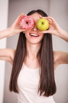 Slim femme tenir dans la main beignet rose et pomme verte