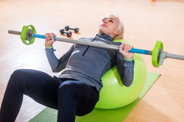 Slim femmes exerçant avec haltères et ballon suisse devant le miroir dans la salle de formation