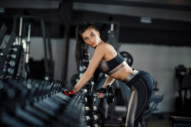 Slim, fille de bodybuilder, soulève un haltère lourd se tenant devant le miroir tout en s'entraînant au gymnase. concept sportif, combustion des graisses et mode de vie sain