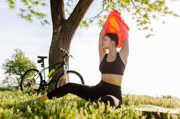 Slim fit belle femme faisant du sport le matin dans le parc sur un tapis de yoga
