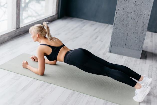 Slim fitnes jeune fille avec queue de cheval faisant des exercices de planche