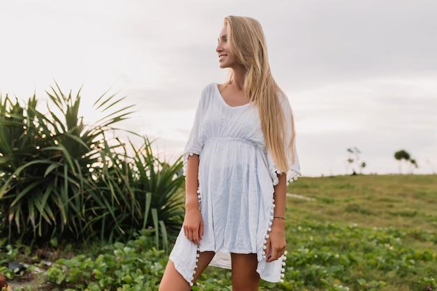 Slim jeune femme aux longs et beaux cheveux blonds vêtus d'une robe blanche posant au coucher du soleil