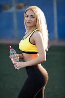 Slim jeune femme buvant de l'eau après la formation